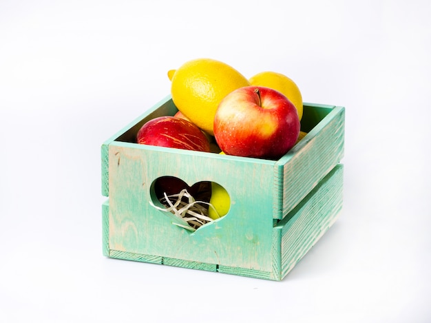 Fresh fruits in wooden box isolated on white