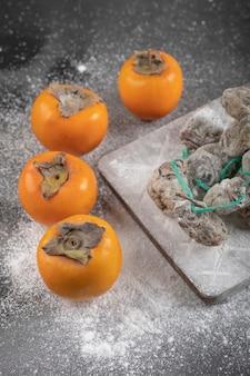 黒い表面に新鮮な富有と干し柿の実