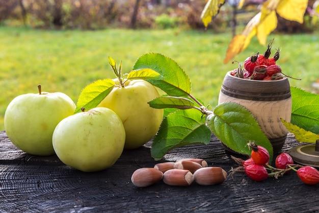 Свежие садовые яблоки и орехи на старом пне.