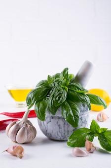 モルタルとオリーブオイル、ニンニク、赤唐辛子、白い背景の上のレモンで新鮮な庭のバジルハーブ。