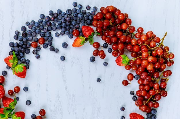 Fresh garden berries and grapes on a white wooden table, horizontal