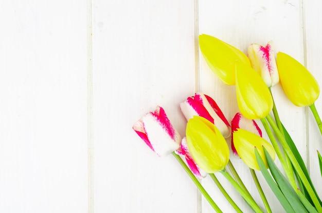 Свежие садовые разноцветные тюльпаны на белом деревянном столе