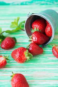 소박한 배경에 양동이에 신선한 정원 딸기, 선택적 초점