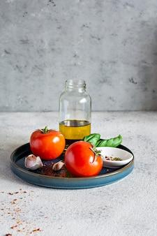 신선한 마늘과 바질 토마토는 구체적인 배경에 접시에 향신료와 올리브 오일을 나뭇잎