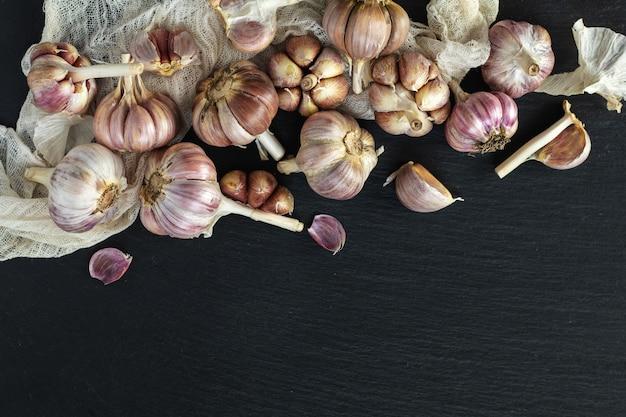 Fresh garlic on a black stone surface