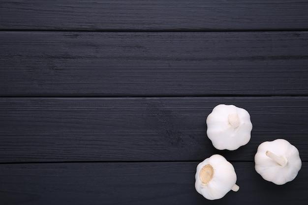 Fresh garlic on a black wooden background