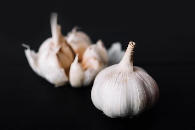 Fresh garlic bulb on black surface