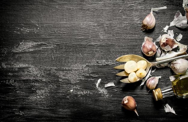 Свежий чеснок в оливковом масле на черном деревенском фоне