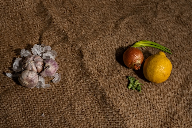 Fresh garlic and other natural cold remedies on sackcloth background