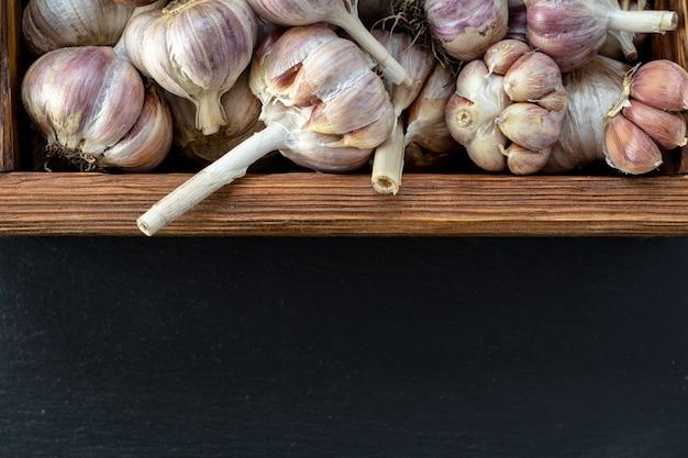 Fresh garlic in wooden box on a black stone surface