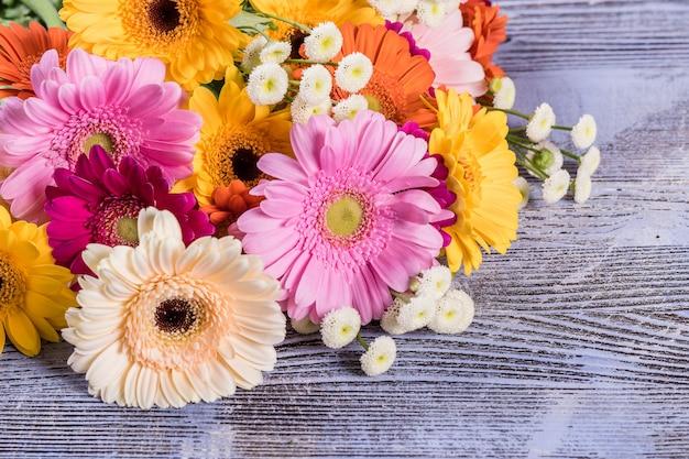 Свежие цветы герберы на деревянном фоне, цветочная рамка, цветочный фон с местом для текста