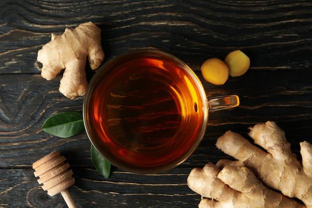 木製の背景に新鮮な生姜とお茶のカップ