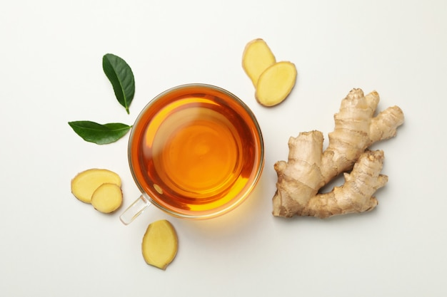 Fresh ginger and cup of tea on white background