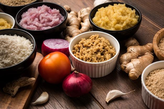 生姜、にんにく、玉ねぎ、トマトピューレは、ヒンディー語でadrak、lahsun、pyaj、tamatarペーストとしても知られています。不機嫌そうな背景の上のボウルに基本的なインド料理の食材