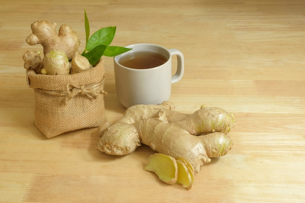 Fresh ginger juice in a cup with orange leaves and pandan leaves on white background