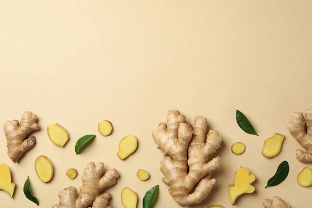Fresh ginger and leaves on beige background