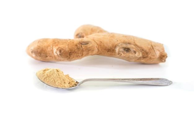 Свежий корень имбиря и имбирный порошок в изолированных ложках, здоровые специи