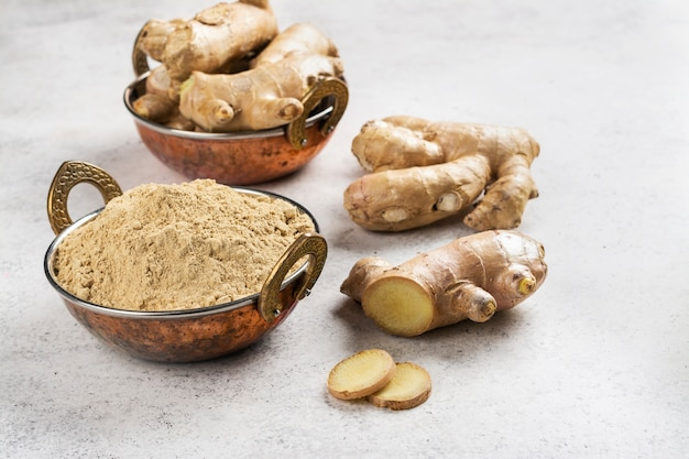 Fresh ginger root and ginger powder in a copper bowl.