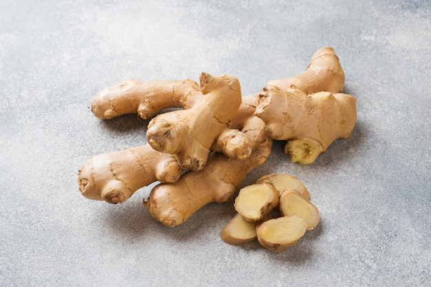 Fresh ginger root on grey surface. .