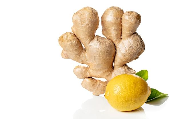 黄色いレモンと緑の葉が白い壁、コピー領域に分離された新鮮なショウガの根