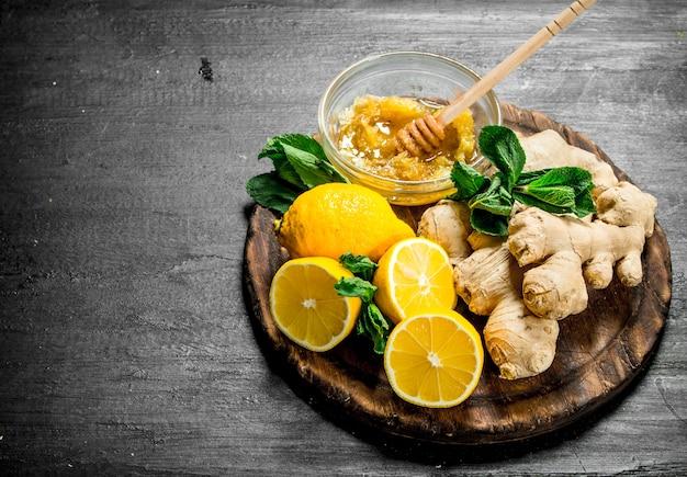 ボード上に蜂蜜とレモンと新鮮な生姜。