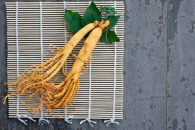 Fresh ginseng root on bamboo basket with green leaves and berries
