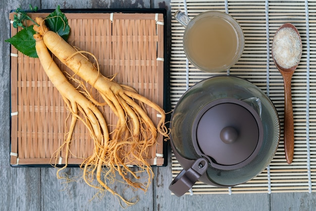 Fresh ginseng root with a cup of hot tea ,the concept of healthy drink
