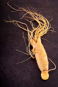 Fresh ginseng roots over dark wooden background ginseng roots herbal medicine on black background