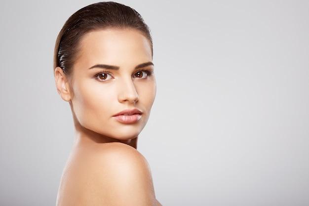 茶色の髪、きれいな新鮮な肌、灰色のスタジオの背景でポーズをとっている裸の肩を持つ新鮮な女の子、明るいヌードメイクのモデル、クローズアップ。