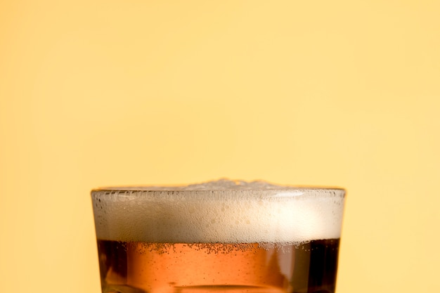 Fresh glass of beer on yellow background