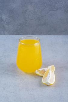 Fresh glass of lemonade with sliced lemon on gray surface