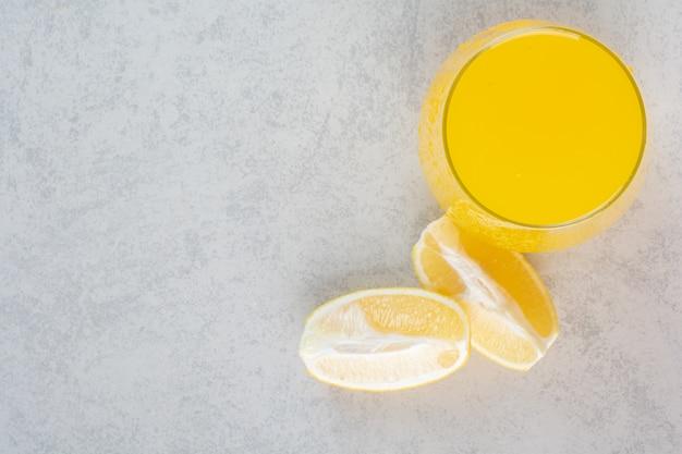 Bicchiere di limonata fresca con fette di limone su grigio.