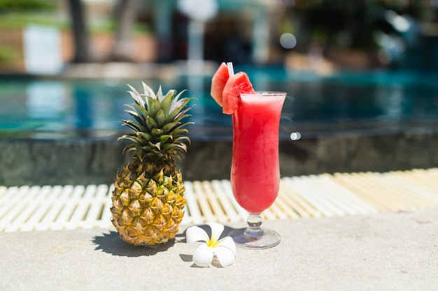 Fresh glass of watermelon smoothie drink, pineapple and tropical plumeria flower standing n