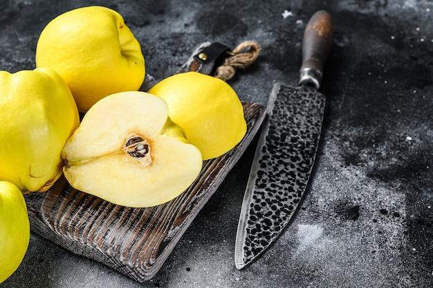 まな板の上に新鮮な金のマルメロの果実。黒の背景。上面図。スペースをコピーします。