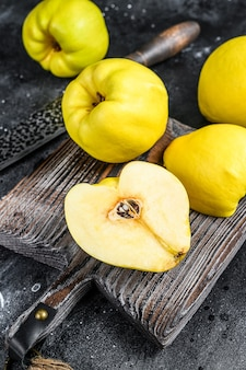 まな板の上に新鮮な金のマルメロの果実。黒の背景。上面図。