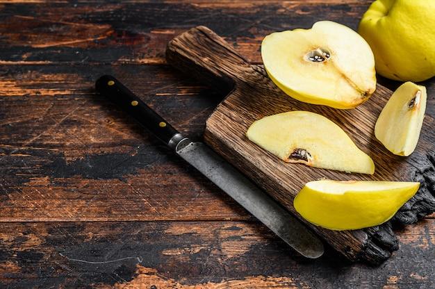 まな板の上に新鮮な金のマルメロの果実。暗い木の背景。上面図。スペースをコピーします。