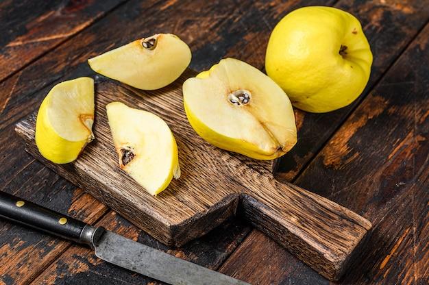 まな板の上に新鮮な金のマルメロの果実。暗い木の背景。上面図。