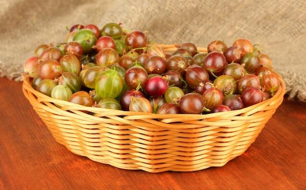 テーブルのクローズアップの籐のバスケットに新鮮なグーズベリー