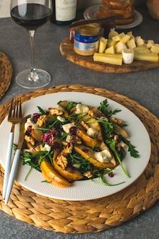Fresh gourmet salad pear, gorgonzola cheese, arugula, walnuts, cheese platter