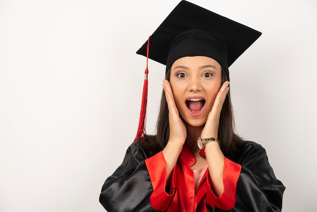 Fresh graduate covering her ears with surprised expression on white background.