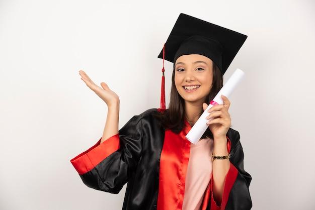 Donna laureata fresca con diploma in posa su sfondo bianco.
