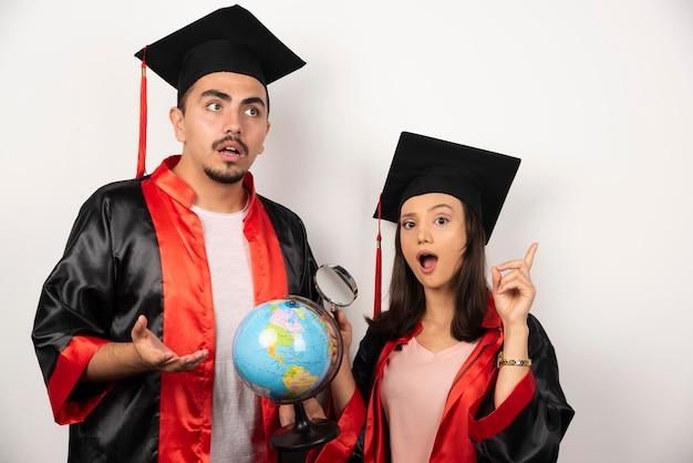 Studenti laureati freschi con il globo che sembra gioioso sul bianco.