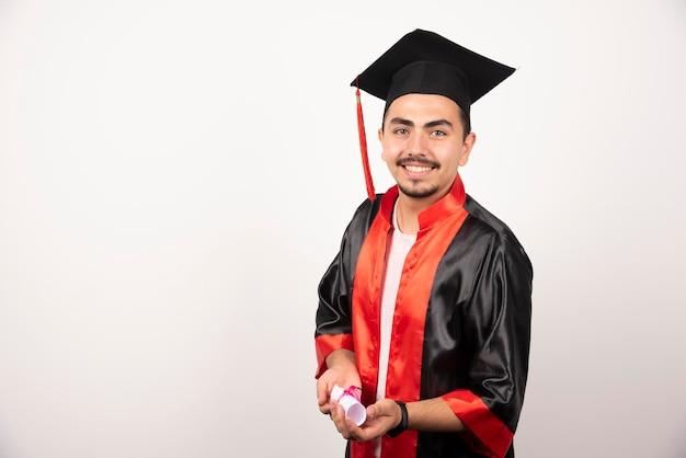 白でポーズをとる卒業証書を持つ新卒。
