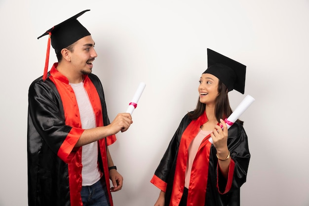 Laureati freschi in abito in posa con diploma su bianco.