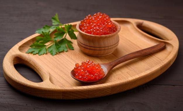 Свежая зернистая красная икра кеты в деревянной тарелке, вкусная и здоровая еда, крупным планом