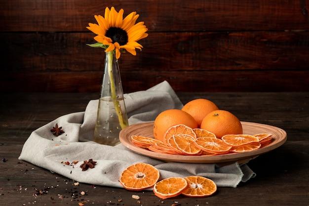 Свежие яблоки бабушки смит, ваза с садовыми цветами, сухими фруктами и звездчатым анисом на клетчатом кухонном полотенце на темном деревянном столе у стены
