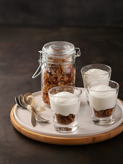 Fresh granola, muesli in a glass with yogurt walnuts, goji berries.