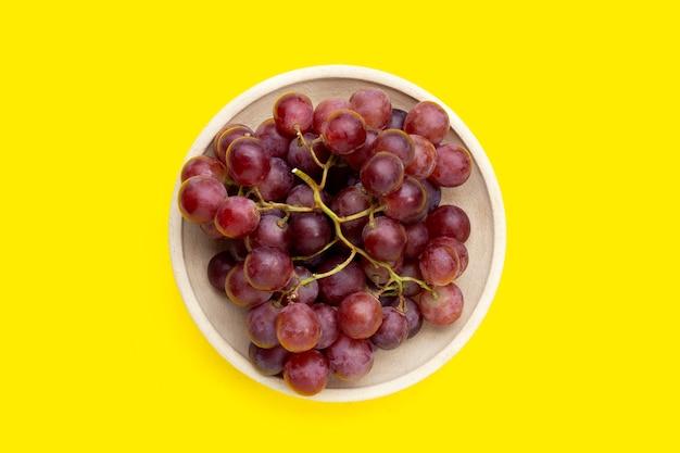 黄色の背景にプレートの新鮮なブドウ。