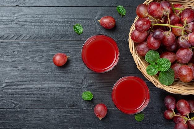 Fresh grape juice on the dark wooden surface.