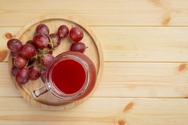 Fresh grape juice on the wooden surface.